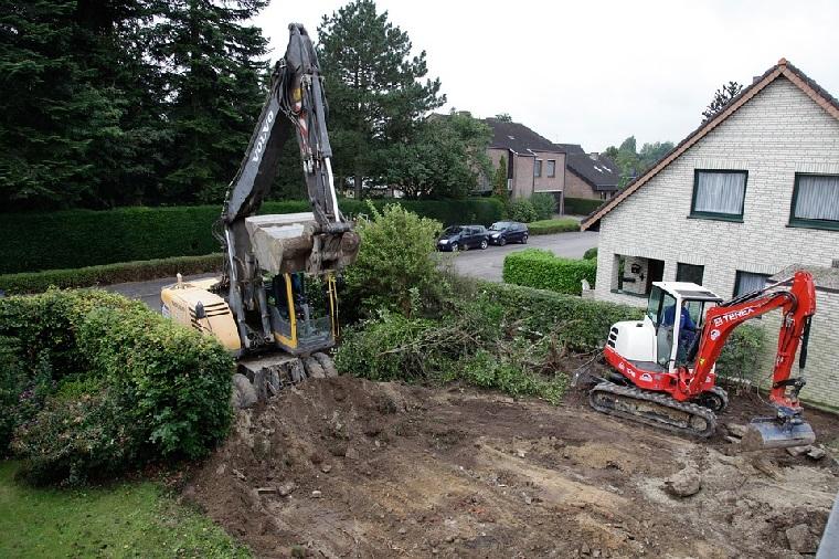 Två grävmaskiner framför ett hus